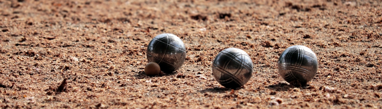 Trois boules de pétanque et un cochonnet sur un terrain de terre