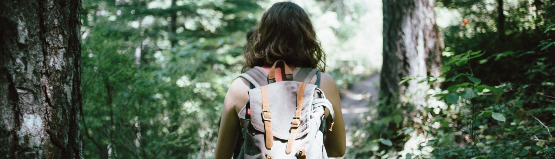 Femme en sac à dos en train de faire une randonnée pédestre dans les bois