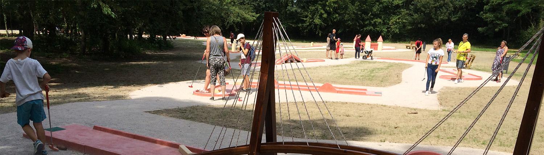 Adultes et enfants jouant sur le mini-golf à 18 trous du site plein air Watissart